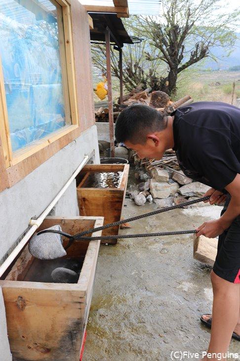 ドツォ(ブータン式お風呂)に石を入れる